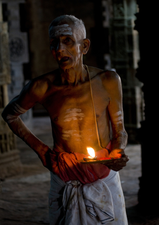 Priest With Traditional Painting On His Forehead Holding A Candle In The Airavatesvara Temple, Darasuram, India