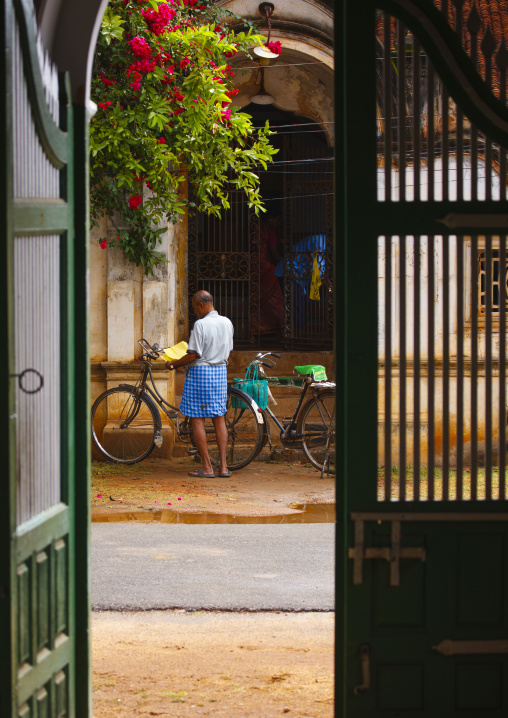 Man And His Bicycle Seen From A Past Old House Entrance In Kanadukathan Chettinad, India