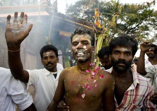Man With Peaks Symbolizing Hindu Gods' Weapons On His Tongue Covered With Ashes And Petals Supported By Friends During Fire Walking Ritual, Madurai, South India