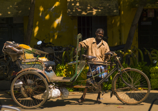 Cycle Rickshaw Driver Posing In Front Of Bunches Of Bananas In A Street Of Pondicherry, India