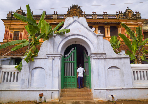 Man Opening The Portal Of A Old Chettiar Mansion With Banana Trees And Carvings Of Hindu Image, Kanadukathan Chettinad, India