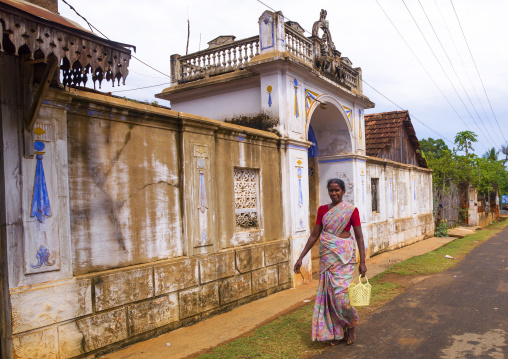 Woman Holding A Plastic Basket In Her Hand Walking Alongside The Gateway Of An Old Chettiar Mansion, Kanadukathan Chettinad, India