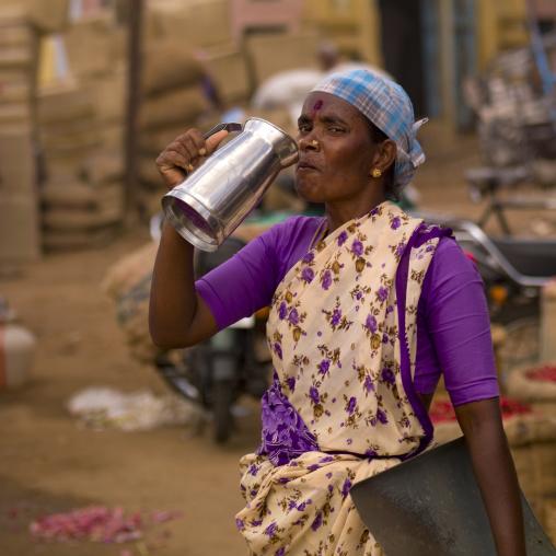 Woman Starring At The Camera While Drinking Water At Madurai Market , India