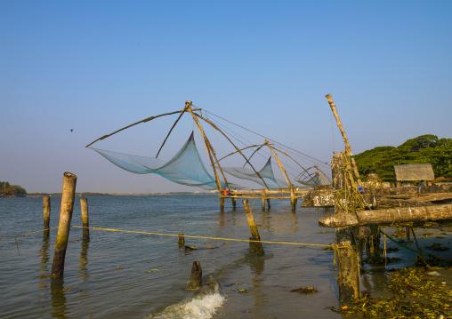 Fishermen Sitting Near Chinese Fishing Nets, Kochi, India