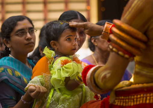 Little Girl With Sandalwood Paste On Her Hairs In  The Arms Of Her Mother Received Blessing From The Theyyam, Thalassery, India
