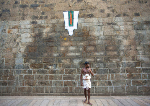 Priest Posing In Front Of A Vaishnava Tilak Painted On A Wall At The Sri Ranganathaswamy Temple, Trichy, India