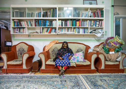 a bandari woman wearing a traditional mask called the burqa sitting in a modern house, Qeshm Island, Salakh, Iran
