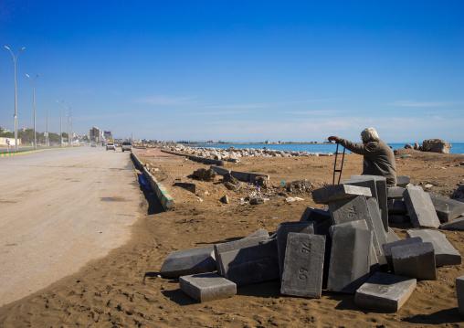 lonely man sit on concrete blocks, Hormozgan, Bandar Abbas, Iran