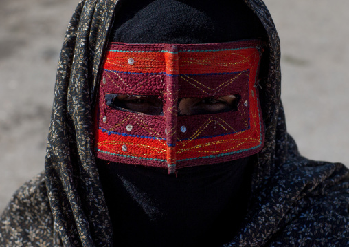 a bandari woman wearing the traditional mask called the burqa on a market, Hormozgan, Bandar Abbas, Iran