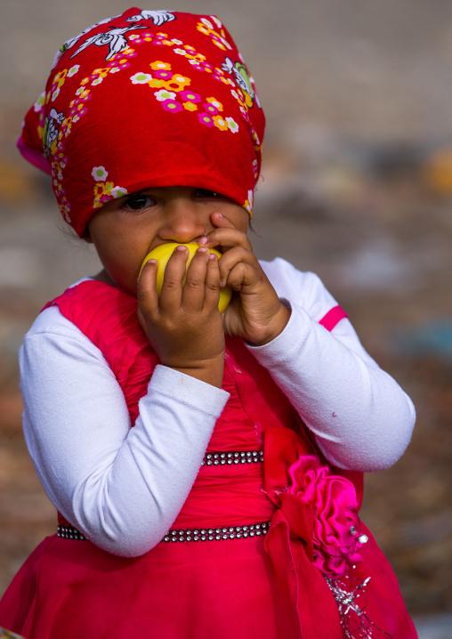 little girl bites in an apple, Hormozgan, Minab, Iran