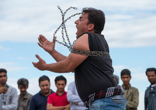 a strongman struggles to break free of chains at the panjshambe bazar thursday market, Hormozgan, Minab, Iran
