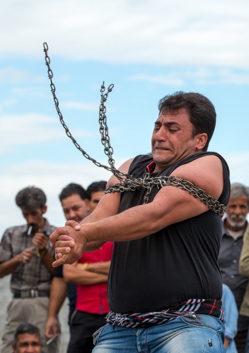 a strongman struggles to break free of chains at the panjshambe bazar thursday market, Hormozgan, Minab, Iran