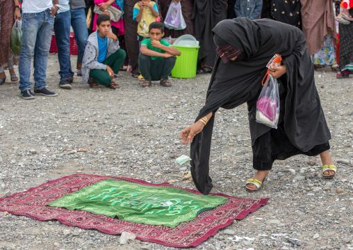 masked woman donating money to the perfomers of a circus, Hormozgan, Minab, Iran