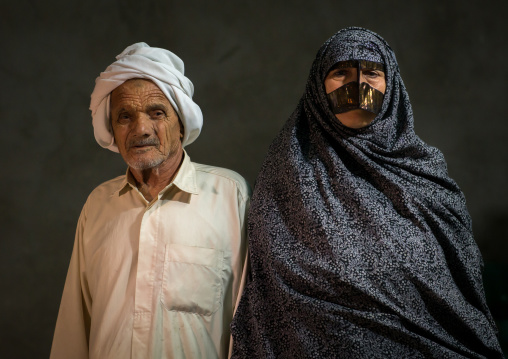 A bandari woman wearing a traditional mask called the burqa with her husband, Qeshm island, Tabl , Iran
