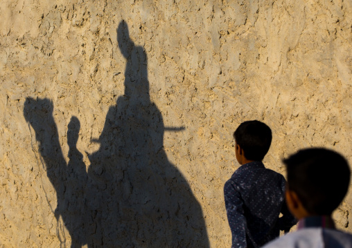 shadow on an adobe wall of the groom riding his camel during a wedding ceremony, Qeshm Island, Salakh, Iran