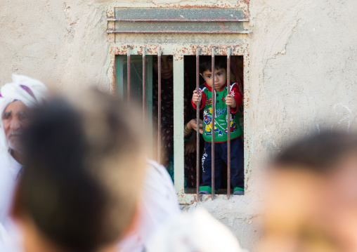 todder boy behing the bars of a window looking in the street, Qeshm Island, Salakh, Iran