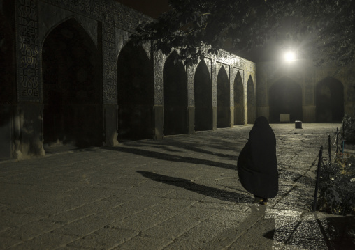 Iranian veiled woman inside sheikh lotfollah mosque at night, Isfahan province, Isfahan, Iran