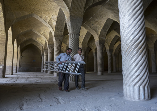 Workers passing in the vakil mosque prayer hall, Fars province, Shiraz, Iran