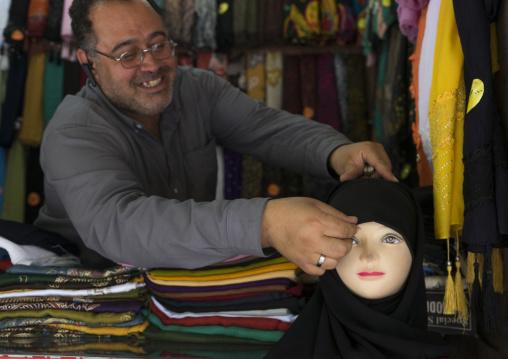 Man putting a veil on a mannequin in the bazaar, Fars province, Shiraz, Iran