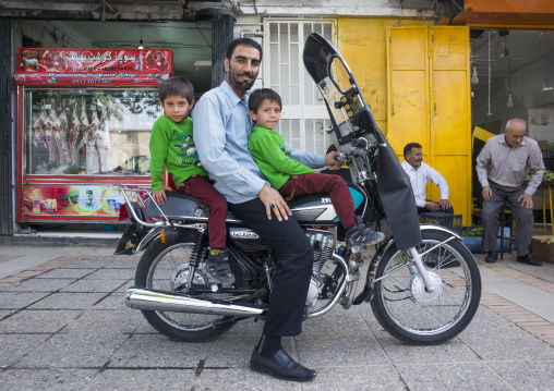 Father with twins on a motorbike, Fars province, Shiraz, Iran