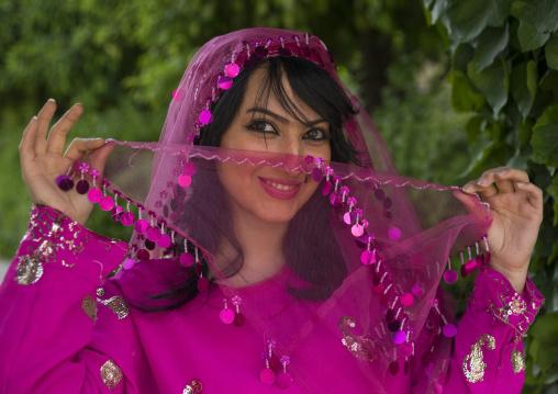 Young woman pausing in narenjestan garden in traditional clothing, Fars province, Shiraz, Iran