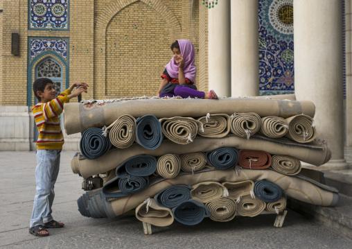 Children playing with carpets in fatima al-masumeh shrine, Qom province, Qom, Iran