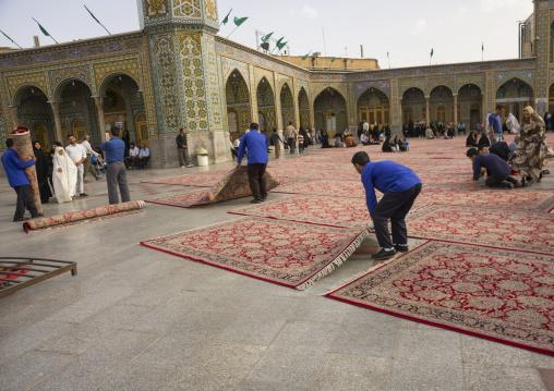 Men putting carpets for praying in the shrine of fatima al-masumeh, Qom province, Qom, Iran