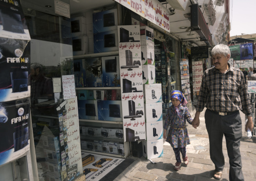 Father and daughter passing in front of an electronics shops, Shemiranat county, Tehran, Iran