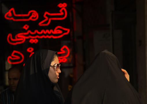 Veiled women in front of red neon lights, Central district, Tehran, Iran