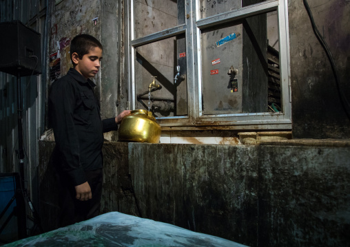 Boy collecting water in a pot to make tea in the bazaar for nazri during muharram, Isfahan province, Isfahan, Iran