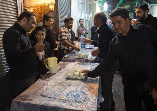 Shiite men offering free milk in the bazaar as nazri during Muharram, Isfahan Province, Isfahan, Iran