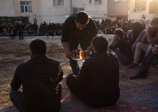 Iranian people drinking tea during a traditional religious theatre called tazieh about imam hussein death in kerbala, Isfahan province, Isfahan, Iran
