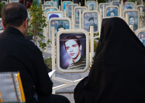 Parents on the tomb of their son killed in the iran iraq war in the rose garden of martyrs cemetery, Isfahan province, Isfahan, Iran