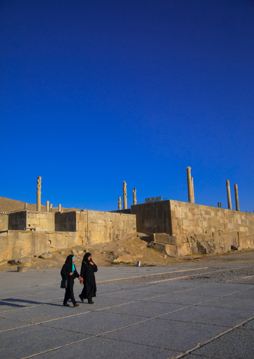 Two iranian women passing in front of the site of Persepolis, Fars Province, Marvdasht, Iran