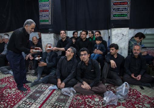 Iranian shiite muslim mourners drinking tea during Muharram inside a hosseinieh, Yazd Province, Yazd, Iran