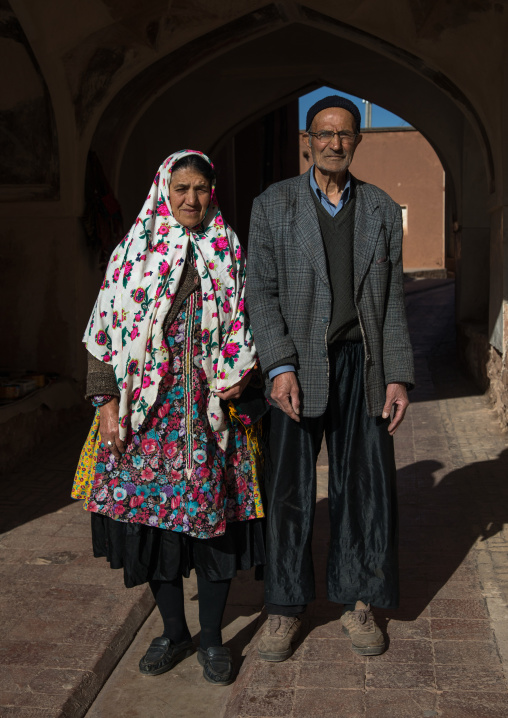 Portrait of an iranian woman wearing traditional floreal chador with her husband in zoroastrian village, Natanz county, Abyaneh, Iran