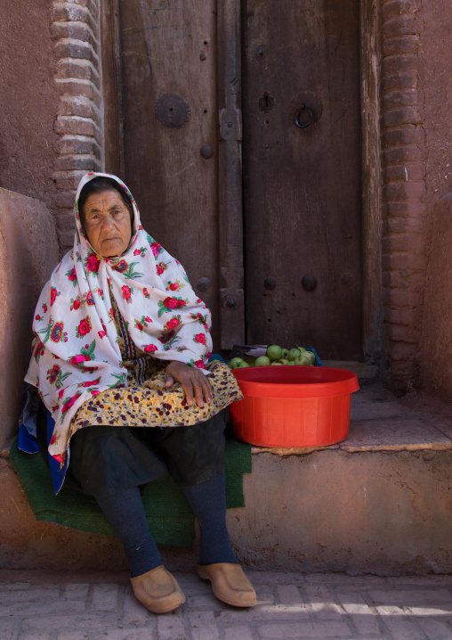 Portrait of an iranian woman wearing traditional floreal chador cooking apples, Natanz County, Abyaneh, Iran