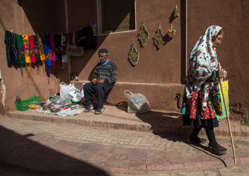 Iranian woman wearing traditional floreal chador and man selling souvenirs for tourists, Natanz county, Abyaneh, Iran