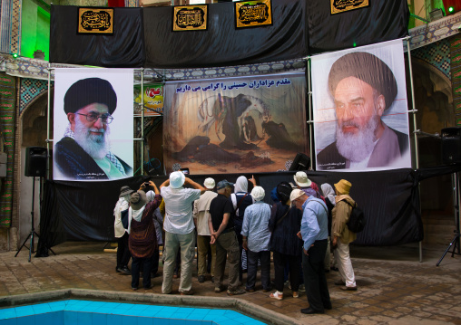 Tourists In Front Of Khameini And Khomeini Posters in the bazar, Isfahan Province, Kashan, Iran