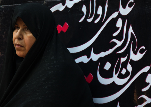 Iranian shiite woman in front of a billboard with calligraphy during muharram to commemorate the martyrdom anniversary of hussein, Lorestan province, Khorramabad, Iran
