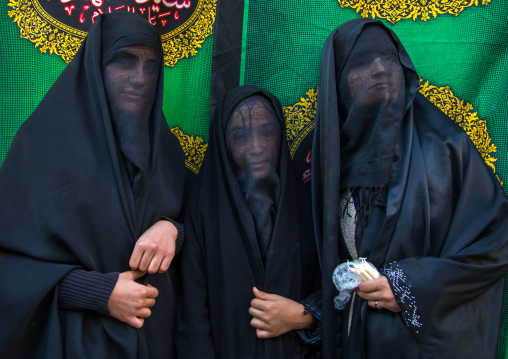 Portrait of iranian shiite muslim women with their faces hidden by a veil mourning imam hussein on tasua during the chehel manbar ceremony one day before ashura, Lorestan province, Khorramaba