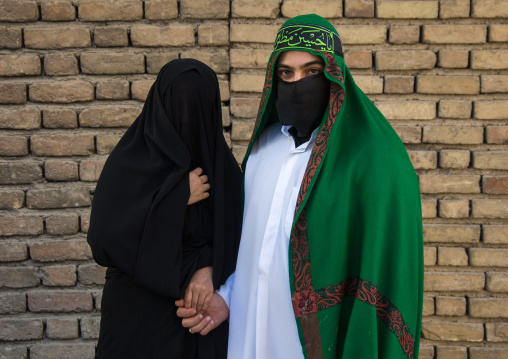 Portrait of iranian shiite muslim couple with their faces hidden by a veil mourning imam hussein on tasua during the chehel manbar ceremony one day before ashura, Lorestan province, Khorramab