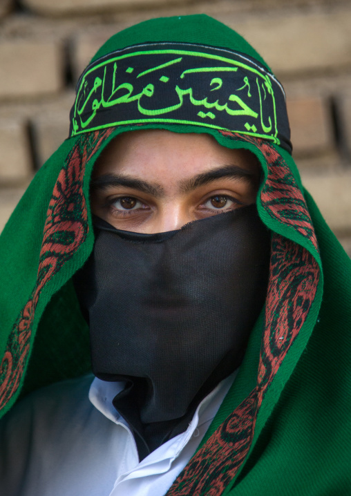 Iranian shiite muslim man with his face hidden by a veil mourning imam hussein on tasua during the chehel manbar ceremony one day before ashura, Lorestan province, Khorramabad, Iran