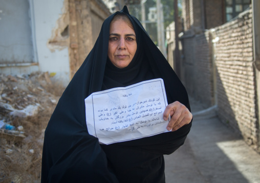 Old woman with a paper saying that thanks to imam hussein a child has been cured after she made a nazri during muharram, Lorestan province, Khorramabad, Iran