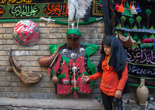 A litle girl stands in front imam hussein clothes during the chehel manbar ceremony one day before ashura, Lorestan province, Khorramabad, Iran