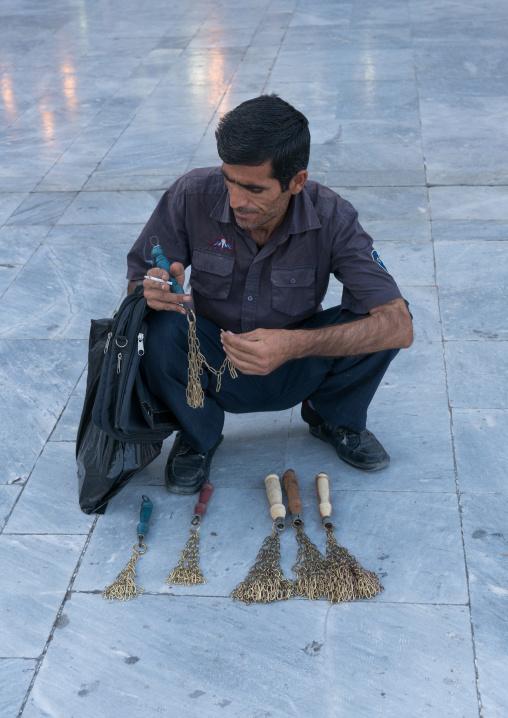 Man selling iron chains for children in fatima al-masumeh shrine during muharram, Central county, Qom, Iran