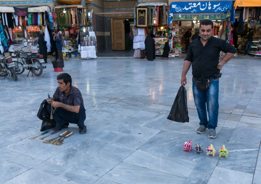 Men selling iron chains for children and toys  in Fatima al-Masumeh shrine during Muharram, Central County, Qom, Iran