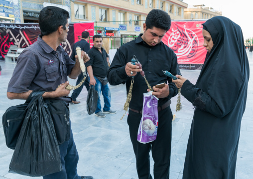 Shiite couple buying iron chains for children in Fatima al-Masumeh shrine during Muharram, Central County, Qom, Iran