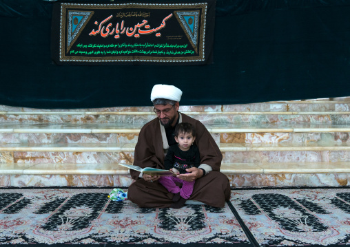 Mullah with his daughter in the Shrine of sultan Ali during Muharram, Kashan County, Mashhad-e Ardahal, Iran