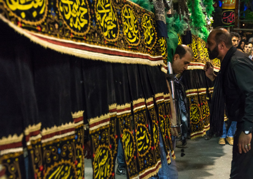 Iranian shiite muslim men carrying an alam during muharram, Lorestan province, Khorramabad, Iran